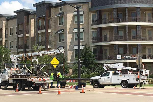 Transportation Department staff work to replace traffic signal controllers at an intersection.