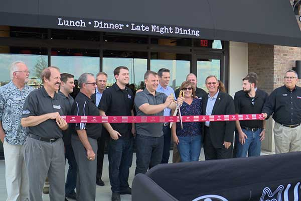 Bar Louie employees, as well as Irving officials, cut the ribbon on the new restaurant, which opened