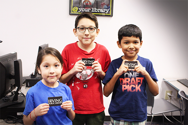 Children show off their new library cards