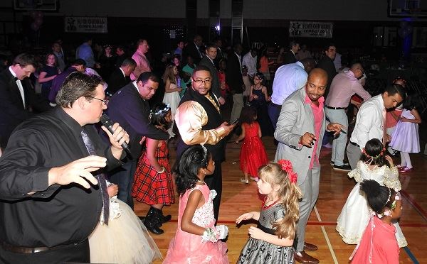 A group photo of girls and their fathers dancing to the DJ music.