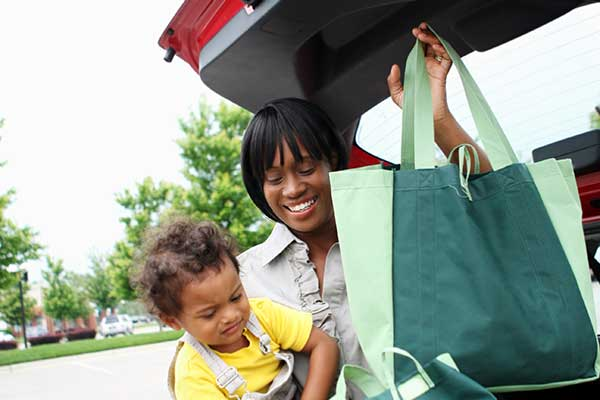 Woman holds a toddler while placing reusable grocery bags in the back of a car.