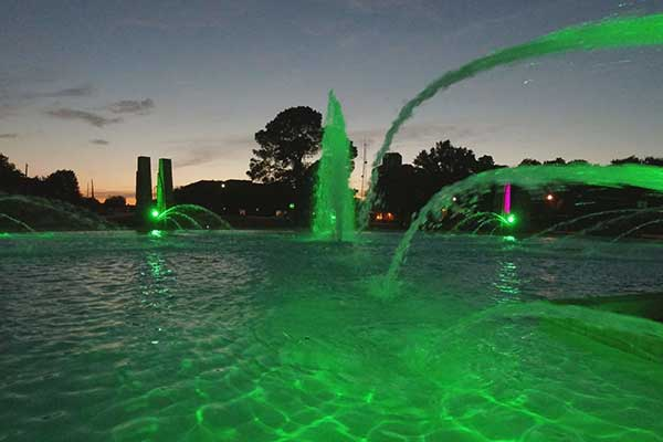 Millennium Fountain in the evening, with green lighting in the water.