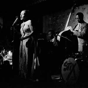 Billie Holiday performing on stage with her band; Paul Quinichette on tenor saxophone.