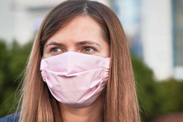 Woman wears pink fabric face mask outdoors.