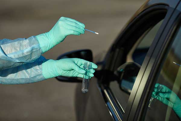 Person administering a COVID-19 test to a customer in a car.