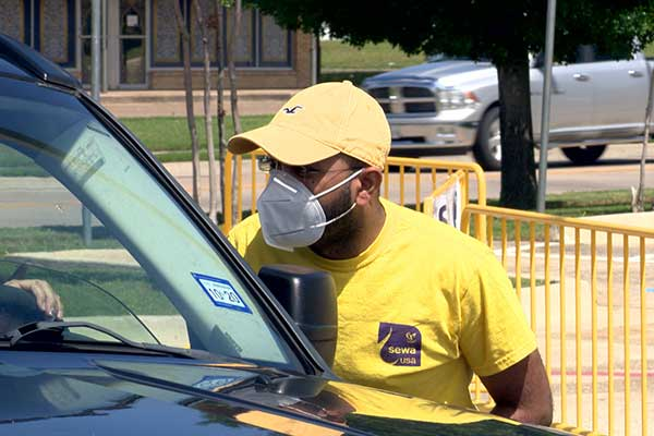 A man wearing a face mask works a food distribution event at the SLPS Community Center.
