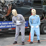 Two crash test dummies standing in front of a crashed car on a trailer